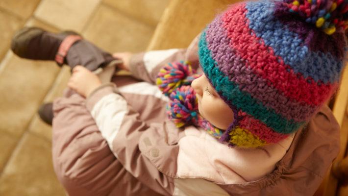 Un jeune enfant vêtu de vêtements d'hiver met ses bottes