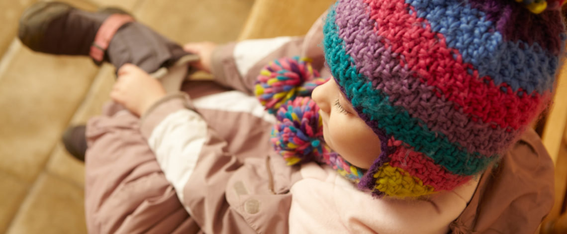 A young child dressed in winter clothing puts on her boots
