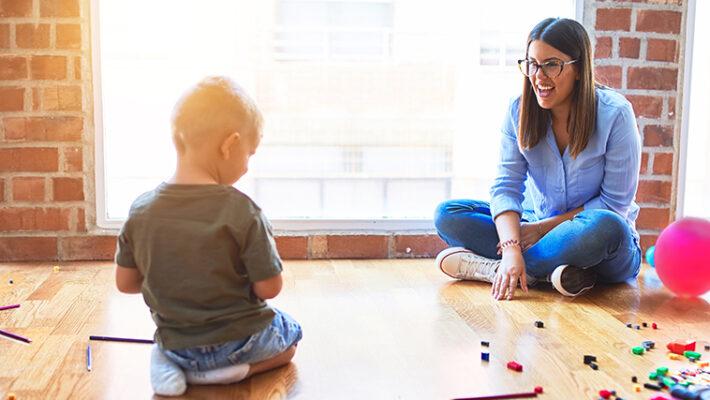 Un enfant et l'EPE jouent sur le sol à une distance de sécurité l'un de l'autre