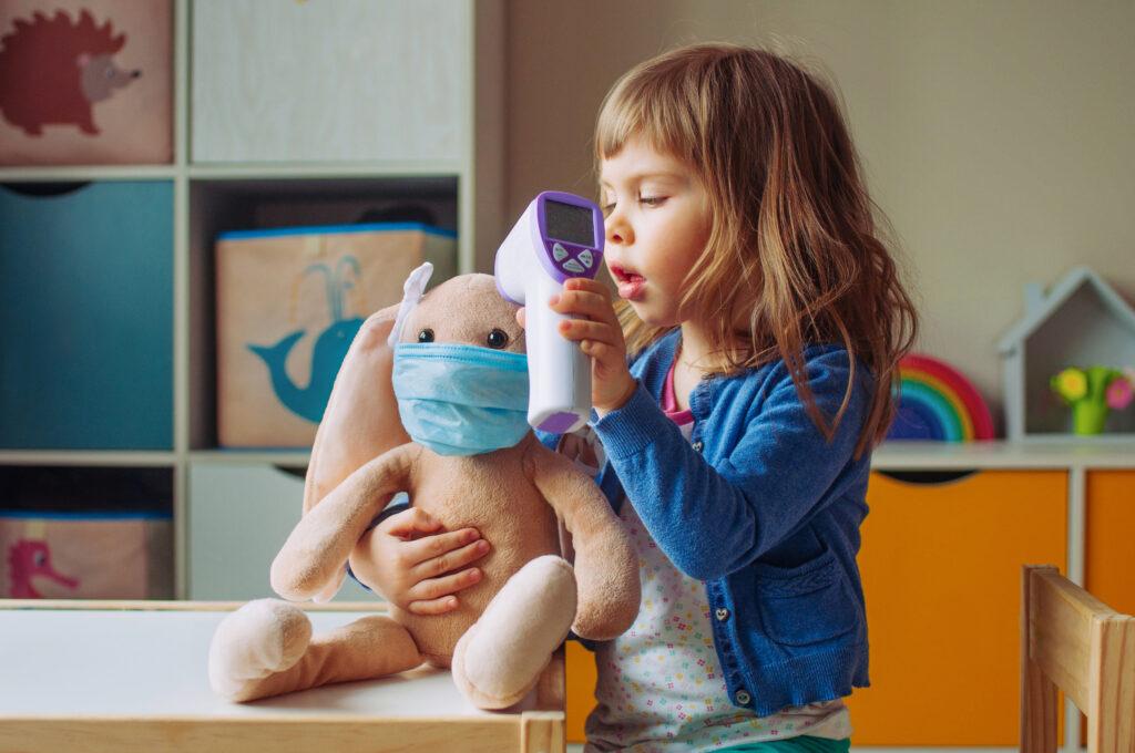 Un enfant joue avec un jouet en peluche dans un masque médical.