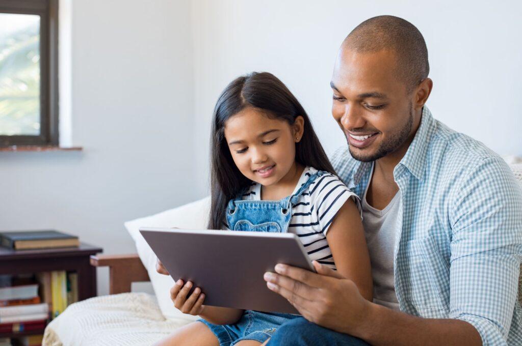 Un enfant et son père sourient en regardant quelque chose sur une tablette