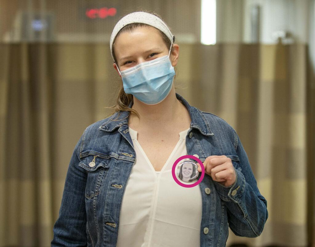 Emily porte un bouton avec son visage dessus pour que les enfants et les familles puissent voir à quoi elle ressemble sous le masque.