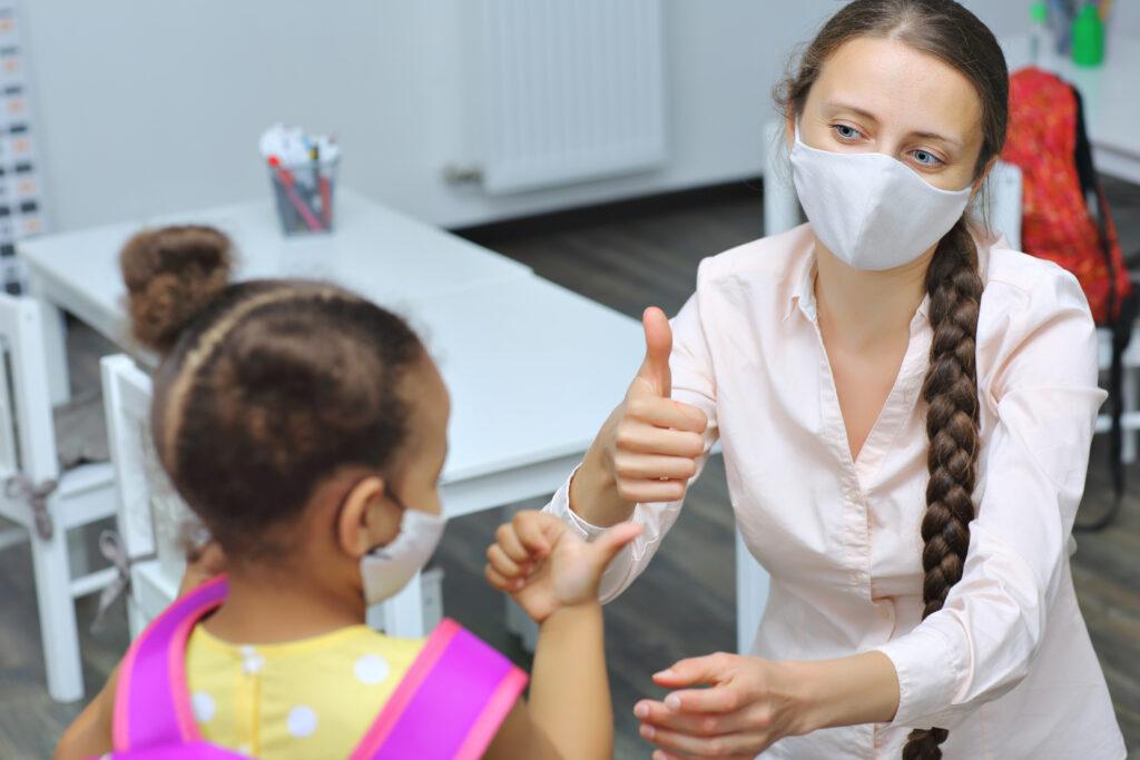 Une éducatrice donne un coup de pouce à un enfant. Elles portent tous les deux des masques médicaux.
