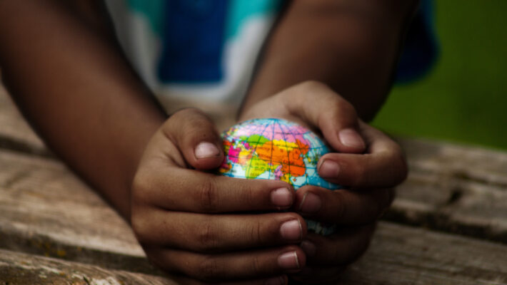 A small child holds a globe in their hands