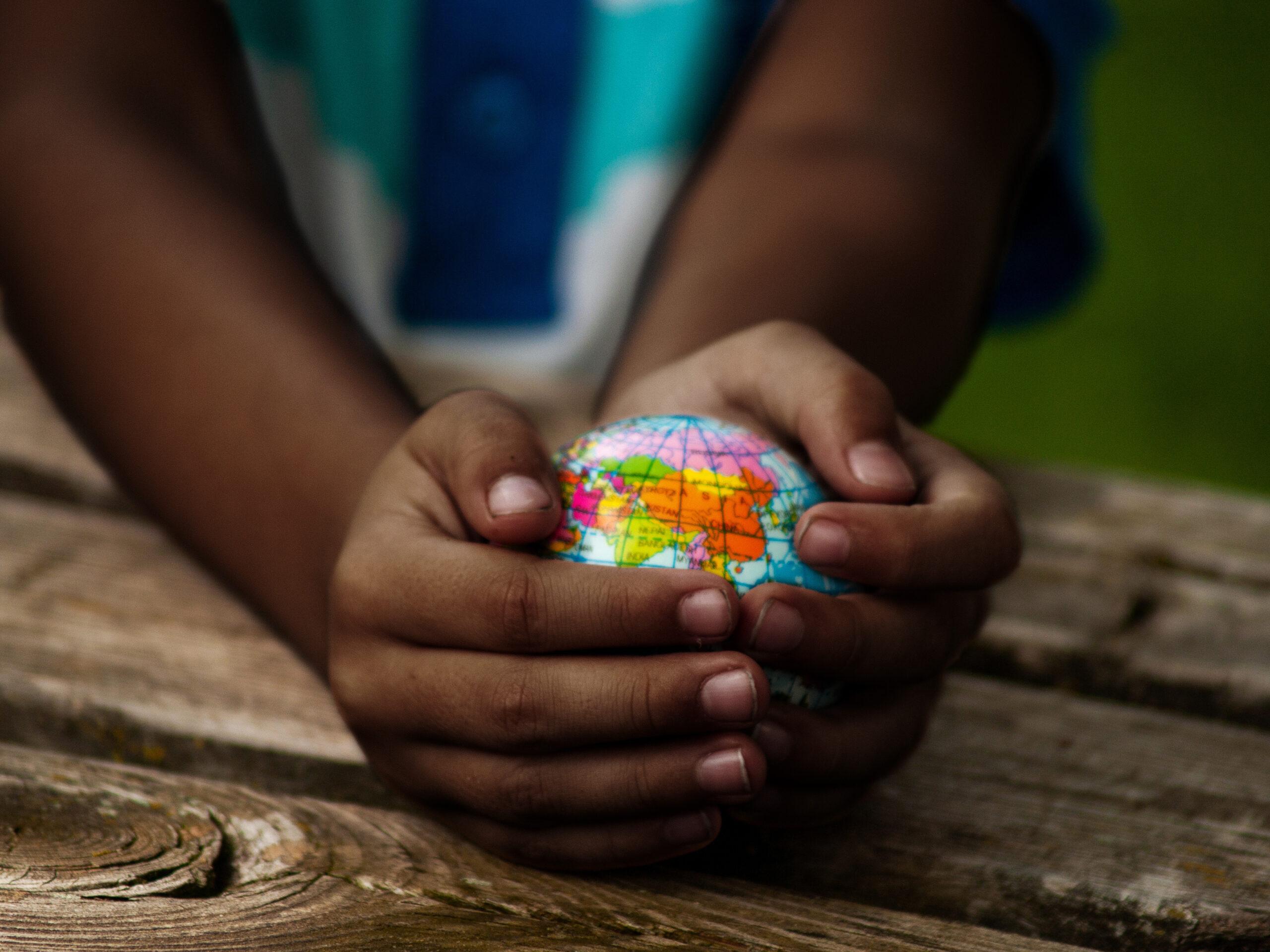Un enfant tient un petit globe dans ses mains