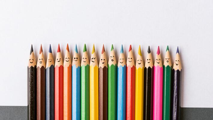 Une rangée de crayons de couleur différente avec des visages souriants