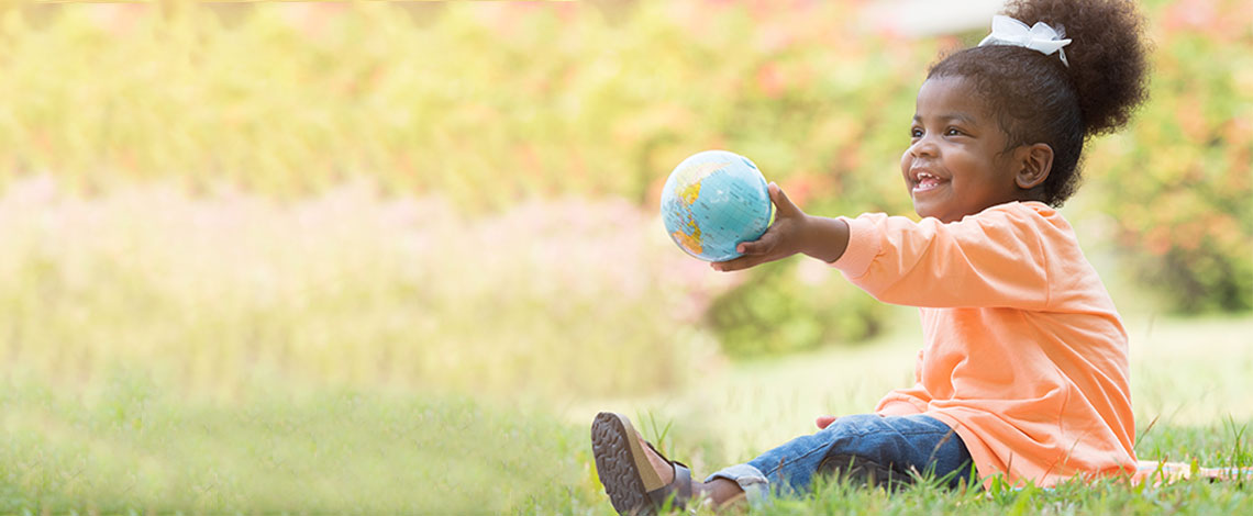 A small child holds a globe