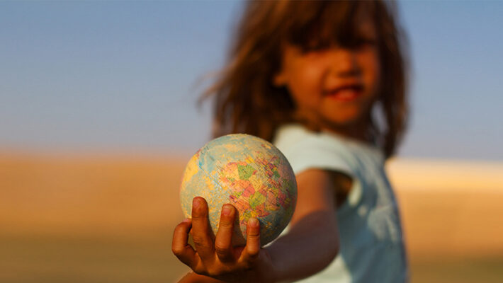 A child holds a globe in an outstretched hand