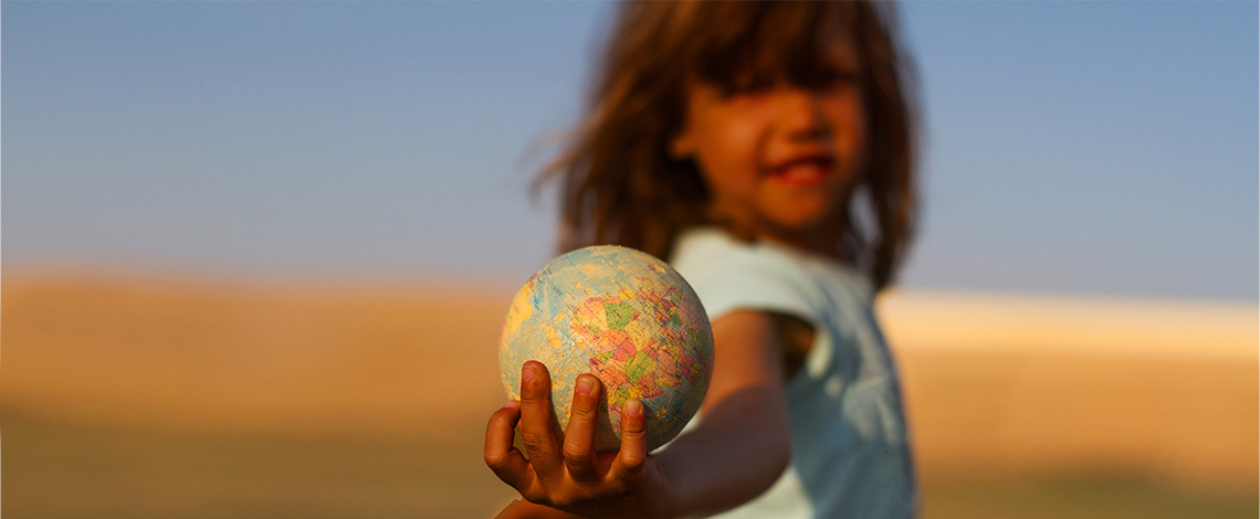 A small child holds a globe in their hand