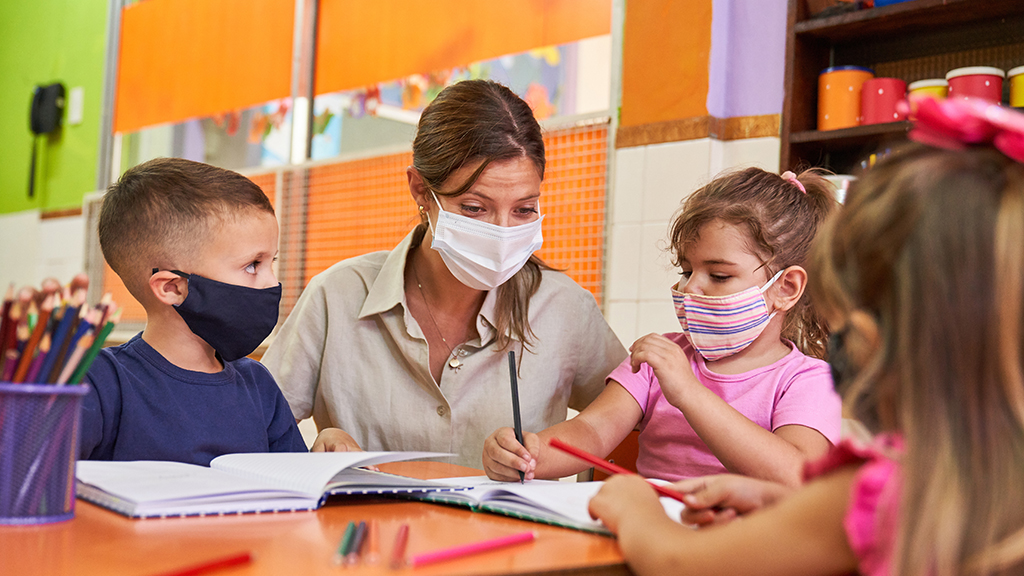 Educator and children with face masks in learning setting.